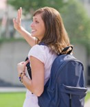 High School girl with backpack waving